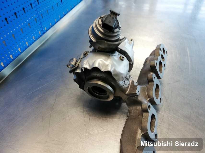 Wyczyszczona w firmie w Sieradzu turbosprężarka do aut  producenta Mitsubishi na stole w laboratorium po remoncie przed spakowaniem