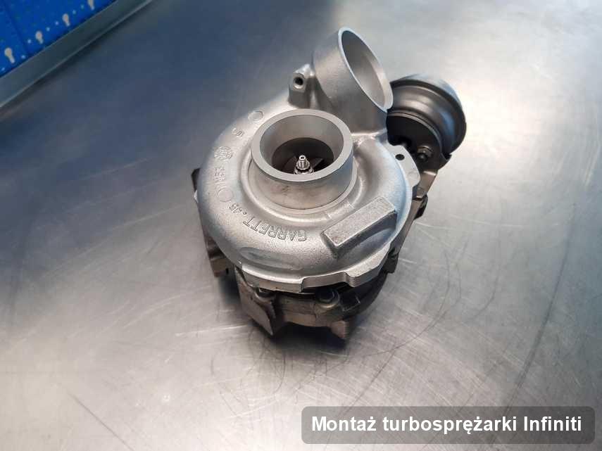 Turbosprężarka do samochodu osobowego sygnowane logiem Infiniti po naprawie w laboratorium gdzie wykonuje się usługę Montaż turbosprężarki